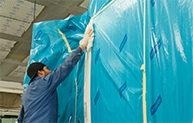 Person putting up blue tarp and taping the seams