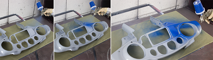 Spraying blue paint on a gray part