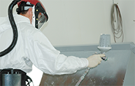 Person in white suit spraying gray paint