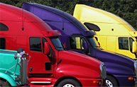 Teal, red, purple and yellow semi trucks lined up