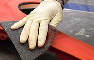 White glove sanding edge of red part