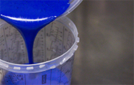 Blue paint pouring into a Sherwin measuring cup
