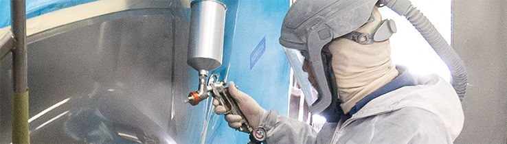 Person in white suit spraying gray over a light blue panel