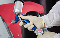Blue spray gun with red panel in the background